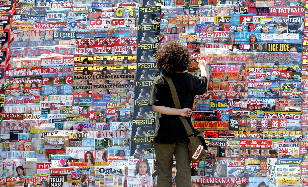 man-standing-in-front-of-magazine-stand-of-headlines